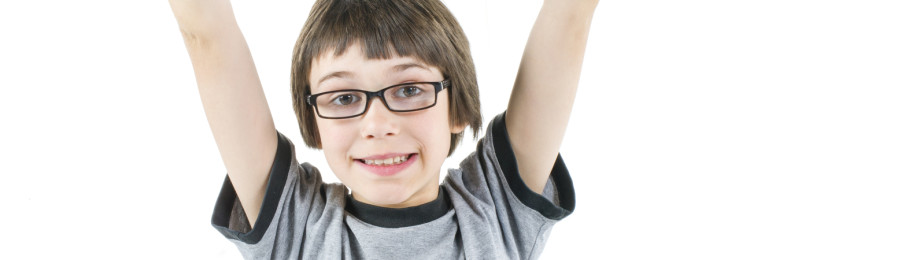 young boy with arms up in the air in grey t shirt with laptop